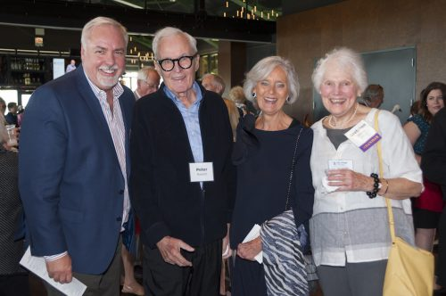 4 individuals at a social function laughing and having a good time