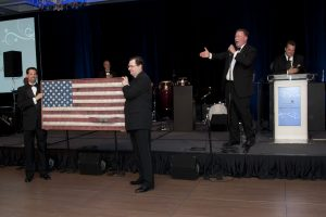 Jim Cornelison sings national anthem while Kevin Riley (left) and Joe O'Connor hold a flag made from decommisioned fire hoses.