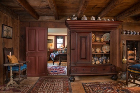 Beautiful woodwork serves as the setting for bright colors, patterned rugs, and an enviable collection of ceramics.