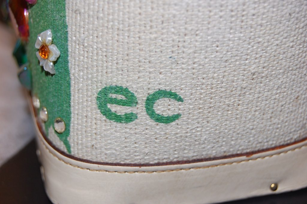The outside of a 1960s canvas bucket handbag, signed with Enid Collins' initials 'ec'.
