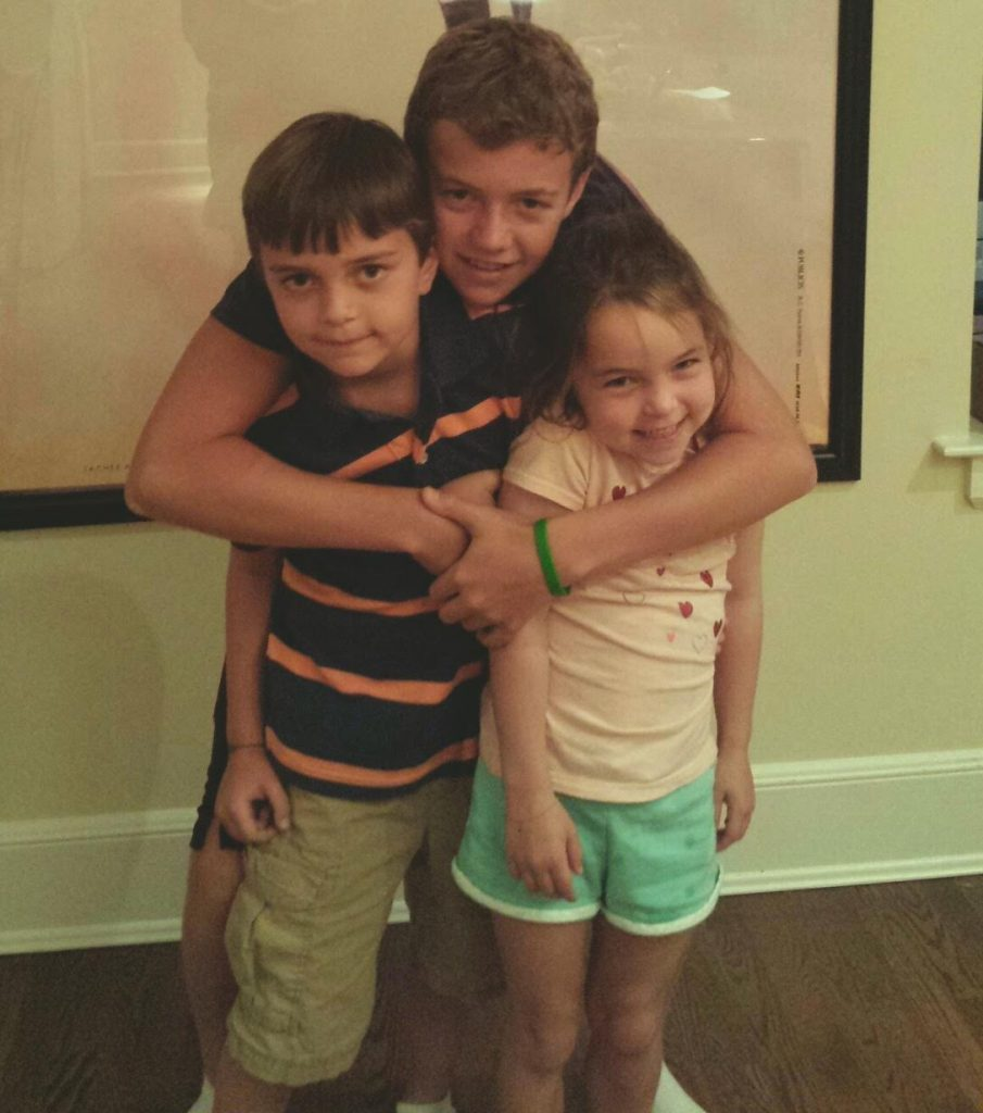 Chrissy's three children, having a sweet sibling moment.