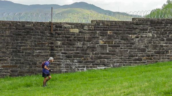 "Barkley ""virgin,"" John Fegyveresi, in a scene from the film, running past the decommissioned Brushy Mountain State Prison during the 2012 Barkley Marathons. A historic prison escape was the inspiration for The Barkley Marathons."