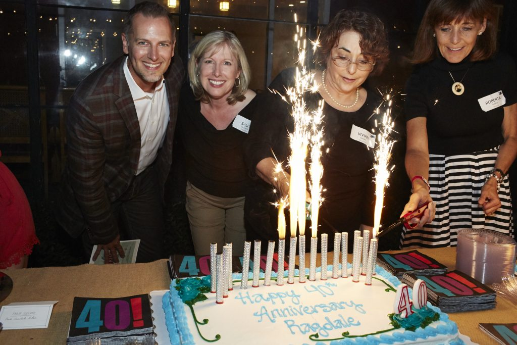 Jeff Meeuwsen, Sally McDonald, Vivian Kramer, and Roberta Haebler light the candles on one of Ragdale's birthday cakes.
