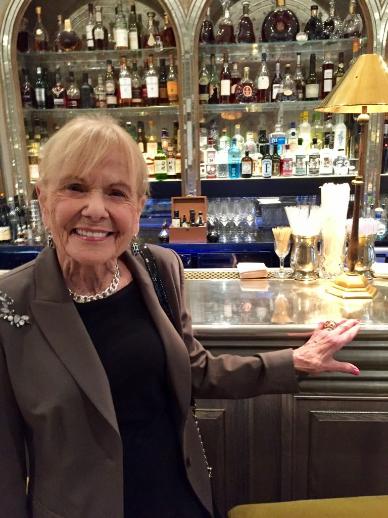 Carlotta stands in front of the well-stocked bar at the Arts Club.