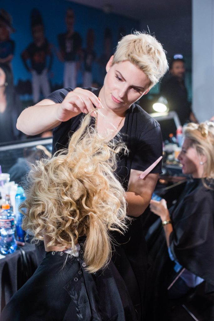 A Salon Buzz stylist creating a runway look for one of the models.