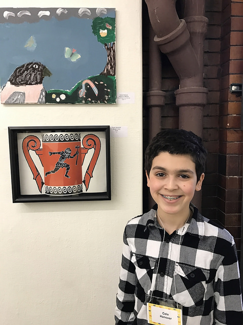 Cole, a young Old Town artist, poses proudly in front of his work.